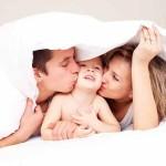 Paar mit Ihrem Baby kuscheln unter einer Decke