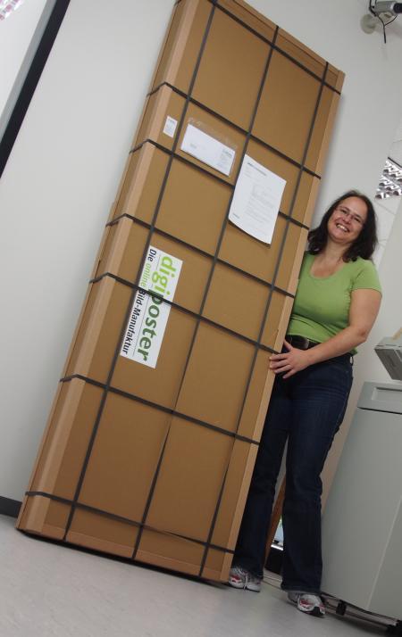digiposter - ein Blick hinter die Kulissen: XXL Paket im Versand. Kundenauftrag mit 2 Stück Leinwandposter auf Keilrahmen im Format 70 x 200 cm, Paket fertig zum Versand auf die Insel Sylt. Unsere Chefin Susanne neben dem extra-großen Paket!